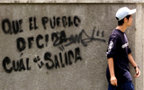 """A man walks past graffiti which reads """"that the town decides the exit,"""" in Caracas, August 16, 2003. Opponents of President Hugo Chavez are pressing for a revocatory or recall referendum on his mandate after August 19, when the constitution allows for such a vote. REUTERS/Howard Yanes"""